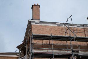 Retour de la façade en fausses briques qui se raccordent avec les vraies. Corbeaux et corniche peints en trompe-l'œil.